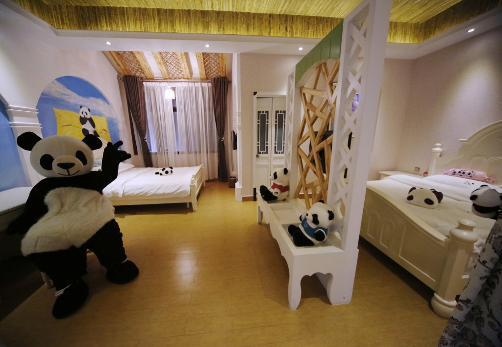 This picture taken on February 22, 2013 shows an employee wearing a panda suit introducing the rooms in a panda-themed hotel at the foot of Emei Mountain in Emeishan, southwest China's Sichuan province. The hotel is reportedly the first panda-themed hotel in the world. CHINA OUT AFP PHOTO (Photo credit should read STR/AFP/Getty Images)